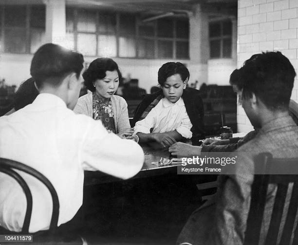 Chinese immigrants play cards while waiting to be called in the immigration offices at Ellis Island USA around 19401950 Before 1924 American...