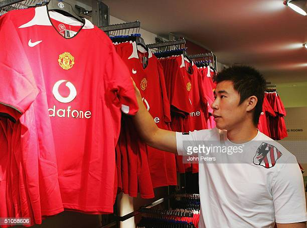 Chinese international Dong Fangzhou of Manchester United ooks at the new Manchester United home kit in the Manchester United Megastore at Old...