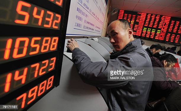 A Chinese investor beside a stock price board showing the red colouring which indicates rising prices at a private securities firm in Shanghai 23...