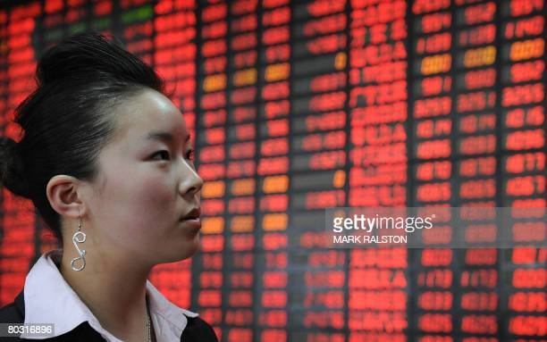 Chinese investor in front of a stock price board showing the red colouring which indicates rising prices at a private securities firm in Shanghai on...