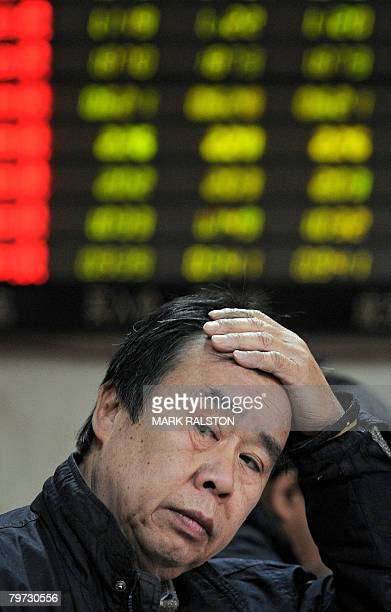 A Chinese investor reacts in front of a stock price board showing the green colouring which indicates falling prices at a private securities firm in...