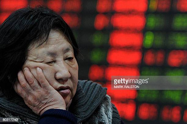 A Chinese investor reacts in front of a stock price board showing the red colouring which indicates rising prices at a private securities firm in...