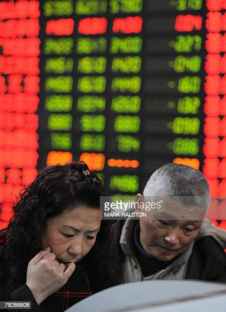 Chinese investors are seen in front of a stock price board showing the green colouring which indicates falling prices at a private securities firm in...