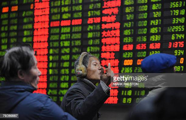 Chinese investors chat in front of a stock price board showing the green colouring which indicates falling prices at a private securities firm in...