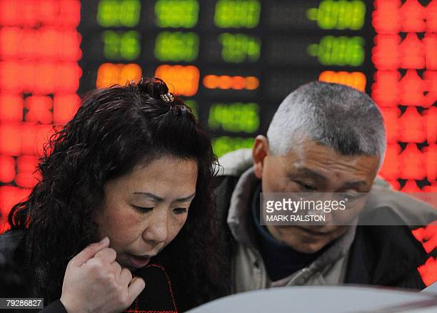 Chinese investors in front of a stock price board showing the green colouring which indicates falling prices at a private securities firm in Shanghai...