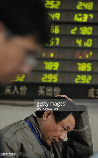 Chinese investors react in front of a stock price board showing the green colouring which indicates falling prices at a private securities firm in...