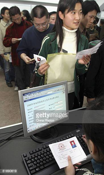 Chinese jobseekers fill in their application forms during a job fair by the local government on November 6 2004 in Xian China More than 20000...