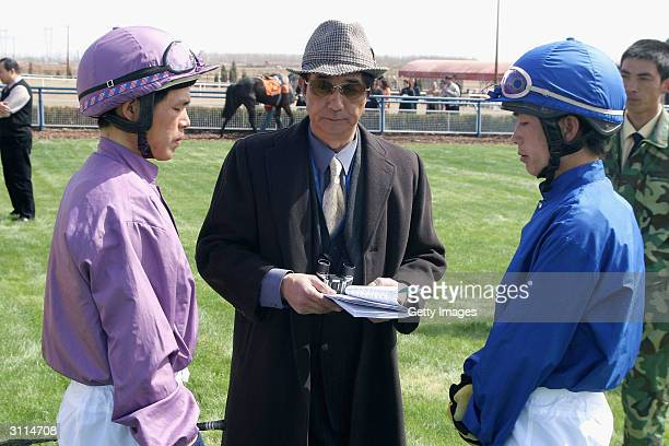 Chinese jockeys listen to their trainer's advice during the Beijing Cup First Heat on March 20 2004 at Beijing Jockey Club Beijing's only racing...