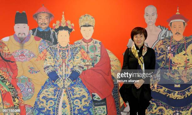 A Chinese journalist standing in front of a poster advertising the exhibition's portrait paintings from China in the Kulturforum at the...