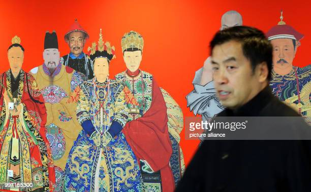 A Chinese journalist walking past a poster advertising the exhibition's portrait paintings from China in the Kulturforum at the Matthaikirchplatz in...