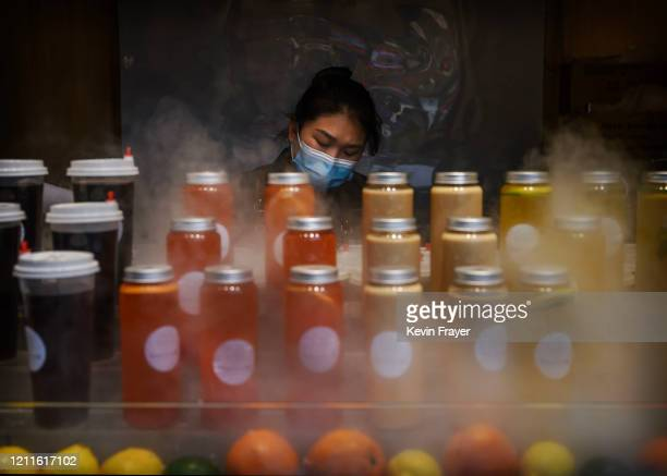 Chinese juice vendor wears a protective mask as she waits for customers in the heat during the May holiday on May 2, 2020 in Beijing, China. After...