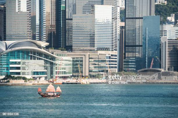 A Chinese Junk touboat sails across the Victoria harbour with the skyscrapers of the Wan Chai district in Hong Kong island