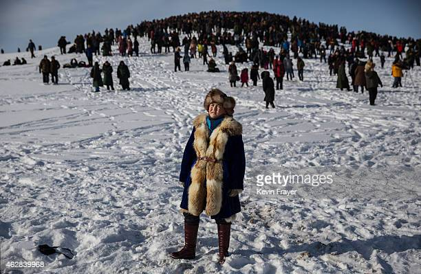 Chinese Kazakh boy watches during a local eagle hunting competition on January 31 2015 in the mountains of Qinghe County Xinjiang northwestern China...