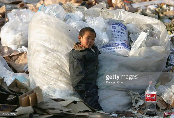 Chinese kid of migrant workers plays at a refuse dump November 23 2004 on the outskirts of Beijing China About four families of Chinese migrant...