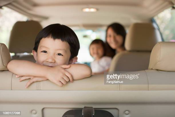 chinese kid sitting in backseat of car - family inside car stock photos and pictures