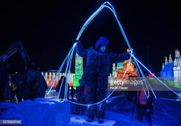Chinese laborer arranges lights to be placed in large ice blocks as he and others work to finish a large ice sculpture in preparation for the Harbin...