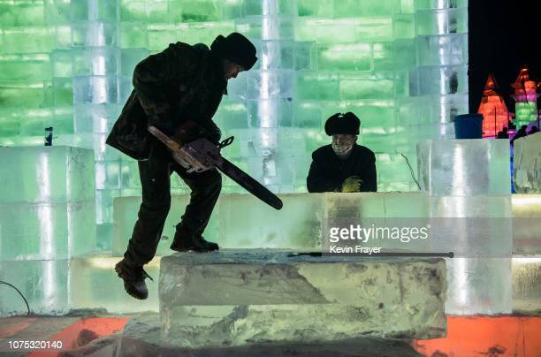 Chinese laborer balances as he readies to cut into a large ice block as he works with others to finish large ice sculptures in preparation for the...