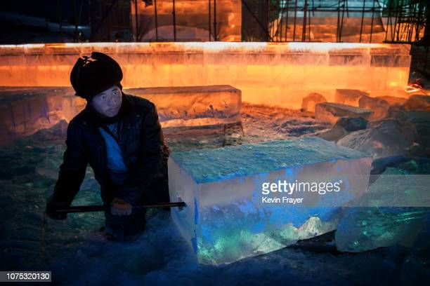 Chinese laborer cuts into a large ice block to place lights as he works with others to finish large ice sculptures in preparation for the Harbin Ice...