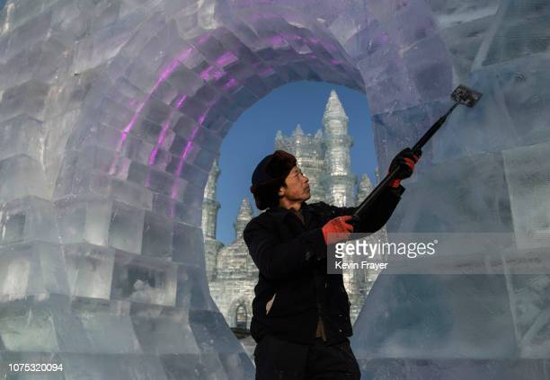 Chinese laborer uses a tool to shave large ice blocks in preparation for the Harbin Ice and Snow Festival on December 22 2018 in Harbin China The...