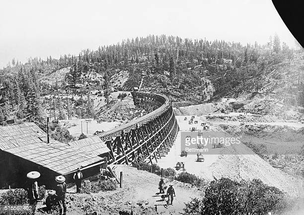 Chinese laborers at work with pick and shovel wheelbarrows and one horse dump carts filling in under the long secret town trestle which was...