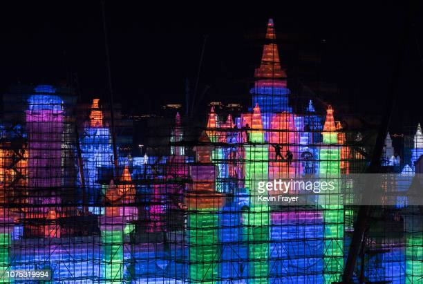 Chinese laborers climb on scaffolding as they work on a large ice sculpture in preparation for the Harbin Ice and Snow Festival on December 19 2018...