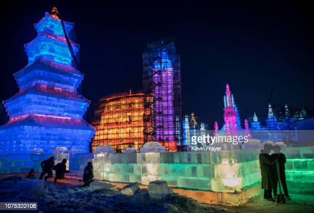 Chinese laborers gather around ice sculptures as they work in preparation for the Harbin Ice and Snow Festival on December 20 2018 in Harbin China...