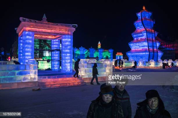 Chinese laborers survey ice sculptures as they work in preparation for the Harbin Ice and Snow Festival on December 20 2018 in Harbin China The...