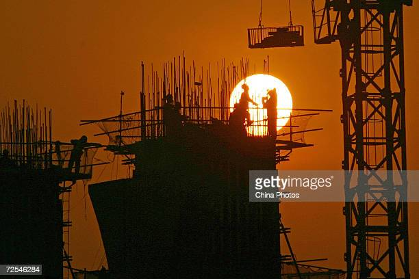 Chinese laborers work at a construction site at sunset March 6 2005 in Chongqing China China's Premier Wen Jiabao announced plans to slow growth in...