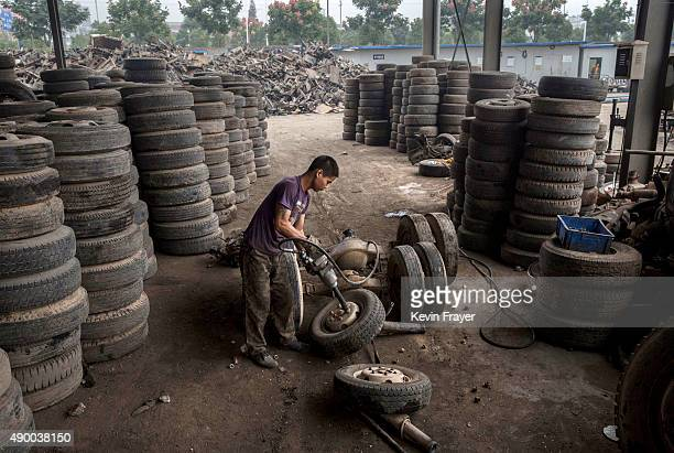 Chinese labourer dismantles wheels from vehicles taken off the road by authorities at an auto scrapyard on September 25 2015 in Zhejiang China The...