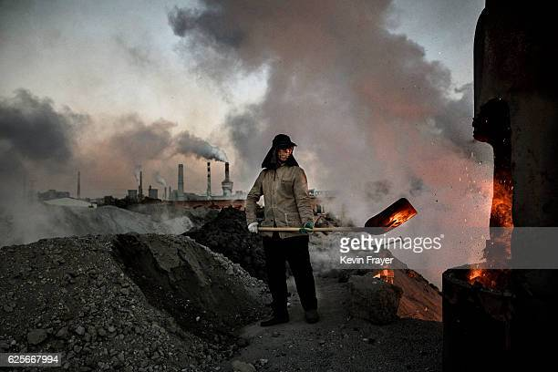 Chinese labourer loads coal into a furnace as smoke and steam rises from an unauthorized steel factory on November 3 2016 in Inner Mongolia China To...