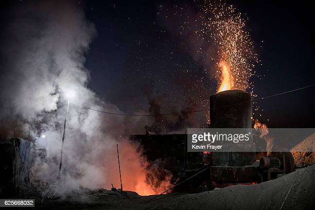 Chinese labourer loads coal into an outdoor furnace at an unauthorized steel factory on November 3 2016 in Inner Mongolia China To meet China's...