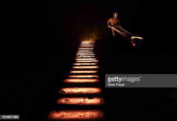 Chinese labourer pours hot steel as he works at an unauthorized steel factory on November 3 2016 in Inner Mongolia China To meet China's targets to...