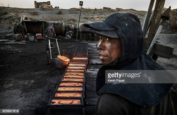 Chinese labourer pours molten steel as another looks on at an unauthorized steel factory on November 3 2016 in Inner Mongolia China To meet China's...