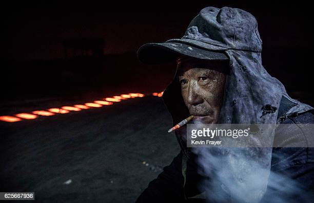 Chinese labourer sits next to red hot steel as he works at an unauthorized steel factory on November 3 2016 in Inner Mongolia China To meet China's...