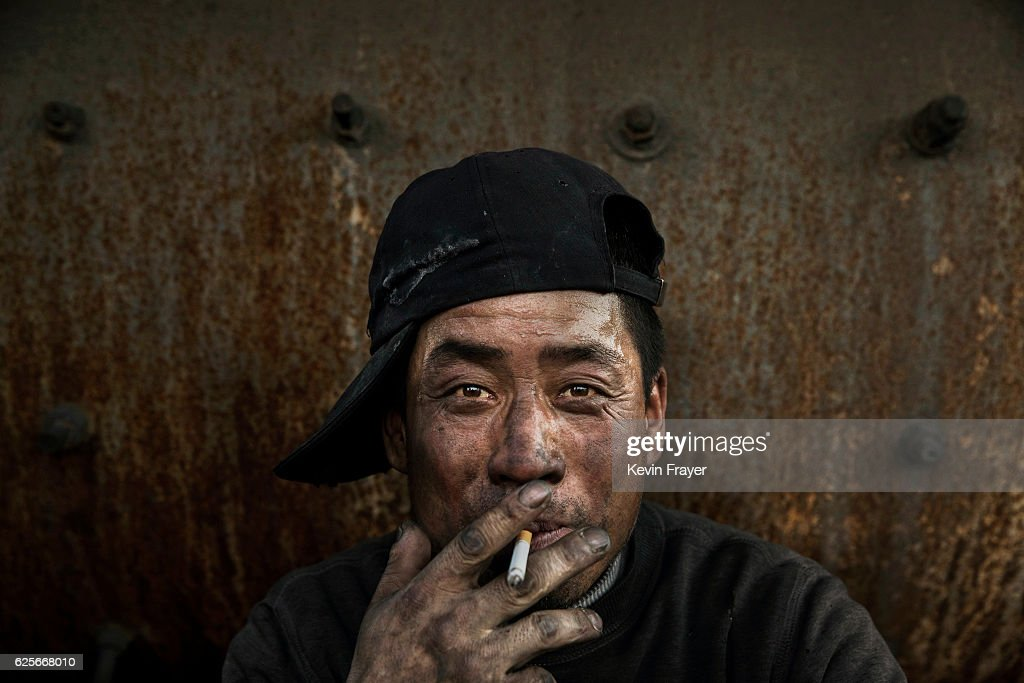 A Chinese labourer smokes as he takes a break at an unauthorized steel factory on November 3, 2016 in Inner Mongolia, China. To meet China's targets to slash emissions of carbon dioxide, authorities are pushing to shut down privately owned steel, coal, and other high-polluting factories scattered across rural areas. In many cases, factory owners say they pay informal 'fines' to local inspectors and then re-open. The enforcement comes as the future of U.S. support for the 2015 Paris Agreement is in question, leaving China poised as an unlikely leader in the international effort against climate change. U.S. president-elect Donald Trump has sent mixed signals about whether he will withdraw the U.S. from commitments to curb greenhouse gases that, according to scientists, are causing the earth's temperature to rise. Trump once declared that the concept of global warming was 'created' by China in order to hurt U.S. manufacturing. China's leadership has stated that any change in U.S. climate policy will not affect its commitment to implement the climate action plan. While the world's biggest polluter, China is also a global leader in establishing renewable energy sources such as wind and solar power.