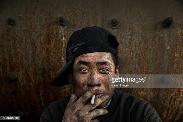Chinese labourer smokes as he takes a break at an unauthorized steel factory on November 3 2016 in Inner Mongolia China To meet China's targets to...