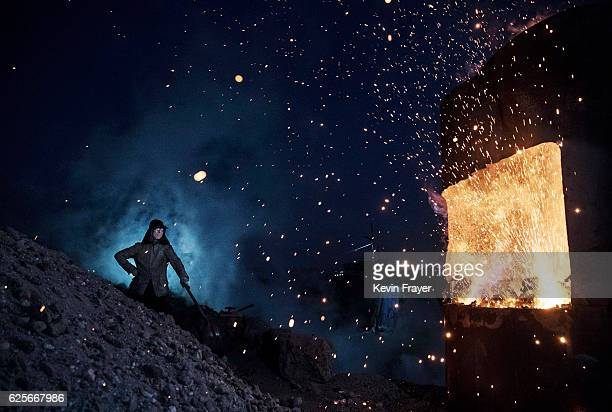 Chinese labourer stands near a furnace as he works at an unauthorized steel factory on November 3 2016 in Inner Mongolia China To meet China's...