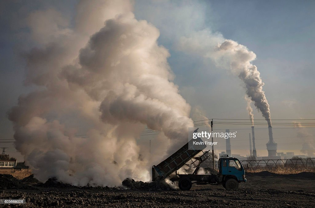 A Chinese labourer unloads waste coal and stone as smoke and steam rises next to an unauthorized steel factory on November 3, 2016 in Inner Mongolia, China. To meet China's targets to slash emissions of carbon dioxide, authorities are pushing to shut down privately owned steel, coal, and other high-polluting factories scattered across rural areas. In many cases, factory owners say they pay informal 'fines' to local inspectors and then re-open. The enforcement comes as the future of U.S. support for the 2015 Paris Agreement is in question, leaving China poised as an unlikely leader in the international effort against climate change. U.S. president-elect Donald Trump has sent mixed signals about whether he will withdraw the U.S. from commitments to curb greenhouse gases that, according to scientists, are causing the earth's temperature to rise. Trump once declared that the concept of global warming was 'created' by China in order to hurt U.S. manufacturing. China's leadership has stated that any change in U.S. climate policy will not affect its commitment to implement the climate action plan. While the world's biggest polluter, China is also a global leader in establishing renewable energy sources such as wind and solar power.