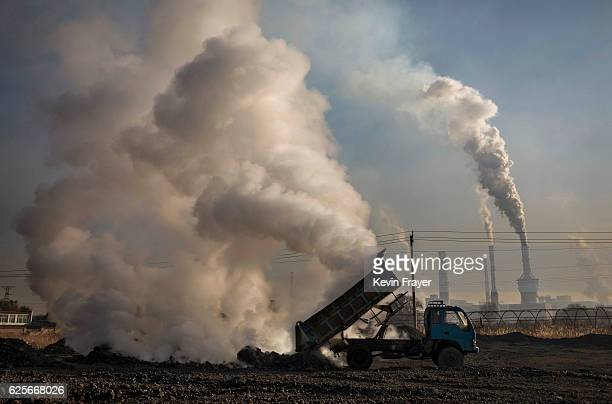 Chinese labourer unloads waste coal and stone as smoke and steam rises next to an unauthorized steel factory on November 3 2016 in Inner Mongolia...