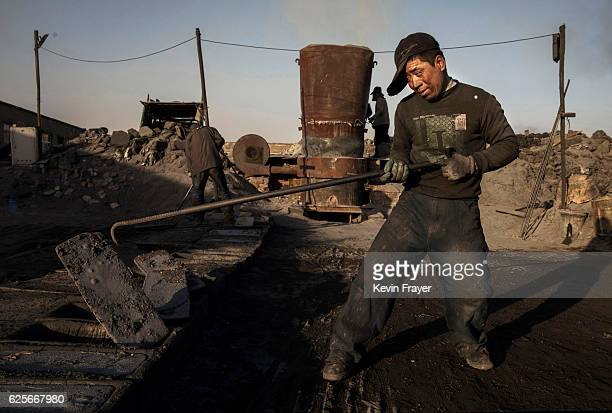 Chinese labourer works next to the furnace at an unauthorized steel factory on November 3 2016 in Inner Mongolia China To meet China's targets to...