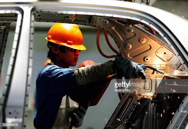 Chinese labourer works on an assembly line at the Zhejiang Geely Automobile Co auto factory on June 9 2005 in Ningbo Zhejiang province China China's...
