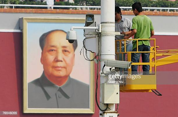 Chinese labourers adjust a surveillance camera at Tiananmen Square ahead of National Day on September 6 2007 in Beijing China The Tiananmen Square is...