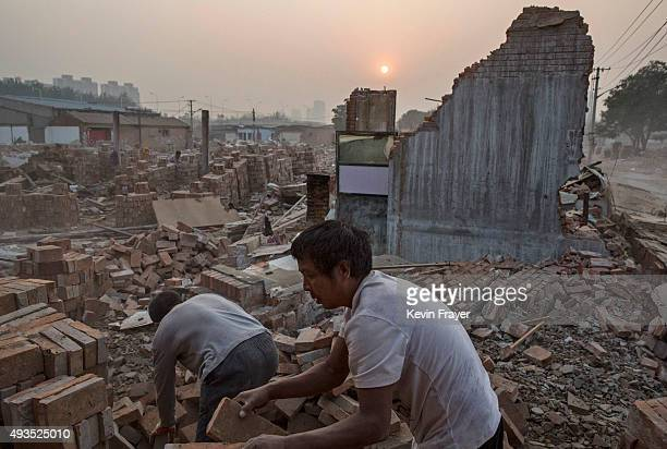 Chinese labourers demolish a house on October 16 2015 in Gucheng Village Tongzhou District Beijing's municipal offices will be moved from the center...