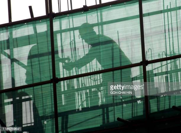 Chinese labourers go about their chores behind the scaffolding of a new construction project in Beijing 10 January 2005 The Chinese government has...