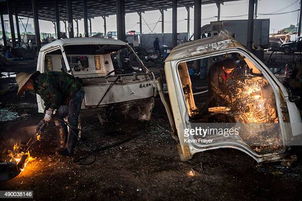 Chinese labourers use welding torches to dismantle trucks that were taken off the road by authorities at an auto scrapyard on September 25 2015 in...