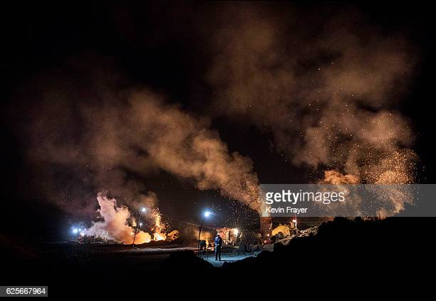 Chinese labourers work as smoke and steam rises from an unauthorized steel factory on November 3 2016 in Inner Mongolia China To meet China's targets...