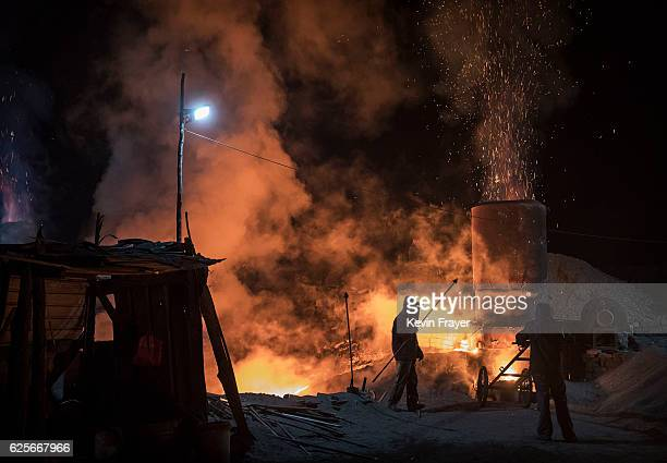 Chinese labourers work at an unauthorized steel factory on November 3 2016 in Inner Mongolia China To meet China's targets to slash emissions of...