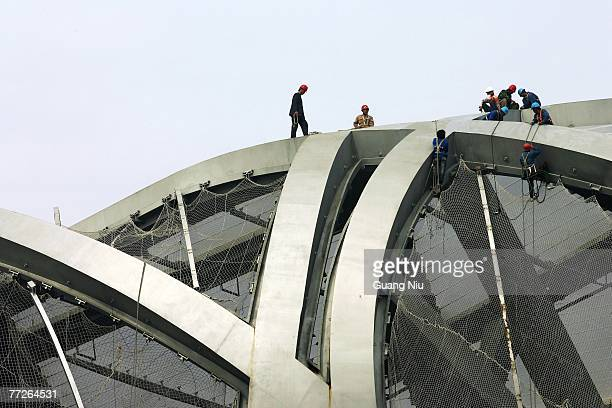 Chinese labourers work at the construction site of the Beijing National Stadium, dubbed the 'Bird's Nest' on October 11, 2007 in Beijing, China. The...