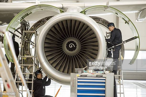 Chinese labourers work at the distribution chain for jet engines as French Prime Minister Manuel Valls visits an Airbus factory in Tianjin on January...