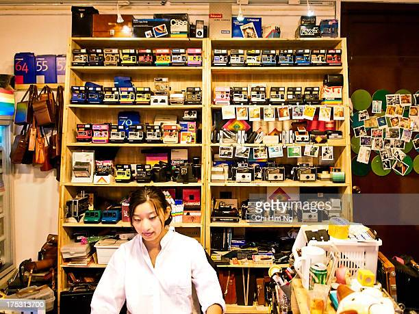 Chinese lady shop keeper working on restoring Polaroid cameras in Shanghai Shot in 2013 Box Polaroid camera and film wall